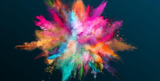 Powder explosion of color on black background. Freeze motion.